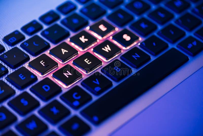 Noticias falsas escritas en un teclado retroiluminado en una luz ambiant azul imágenes de archivo libres de regalías