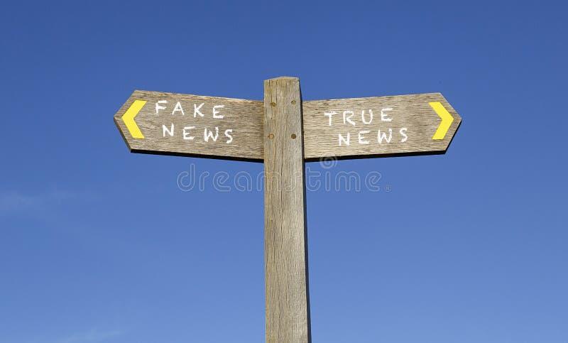 Noticias falsas y noticias verdaderas - poste indicador del concepto foto de archivo