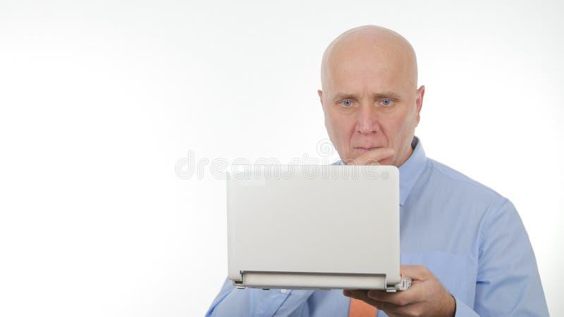 Noticias financieras de Image Reading Bad del hombre de negocios serio en el ordenador portátil foto de archivo libre de regalías
