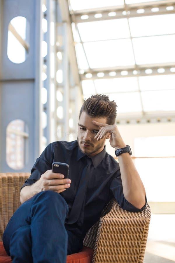 Noticias financieras de lectura del CEO del varón pensativo en sitio web vía el teléfono móvil durante rotura de trabajo en compa foto de archivo libre de regalías