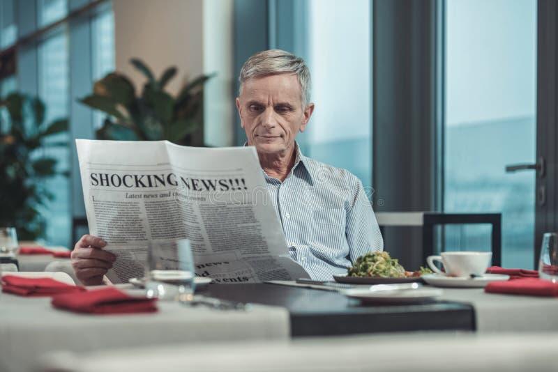 Noticias impactantes de lectura encantadas del pensionista sobre base diaria fotos de archivo