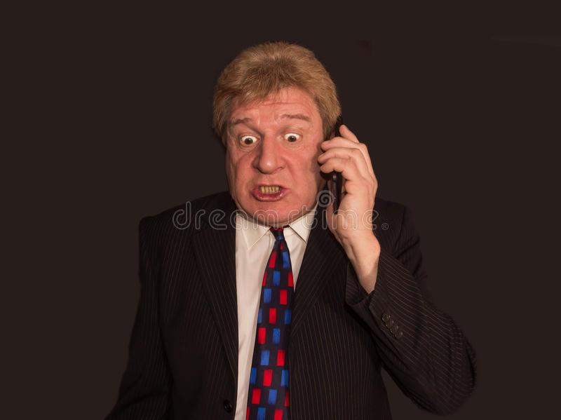 Noticias impactantes Hombre maduro sorprendido en traje con el teléfono móvil foto de archivo libre de regalías
