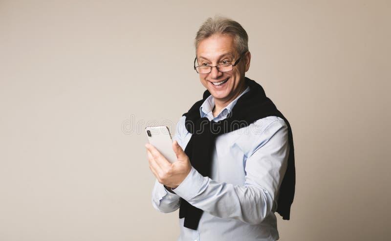 Noticias mayores felices de la lectura del hombre de negocios en smartphone foto de archivo