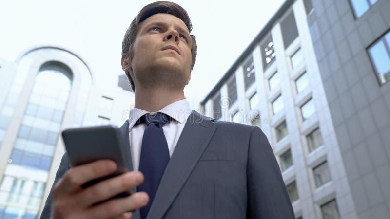 Noticias pensativas jovenes de la lectura del agente en el smartphone, recibiendo la información más reciente foto de archivo