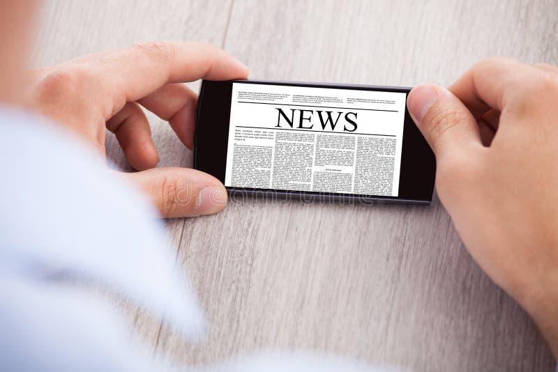 Noticias que practican surf del hombre de negocios en smartphone en el escritorio imagenes de archivo