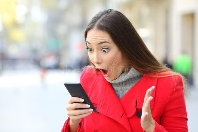 Noticias sorprendentes de la lectura de la mujer en línea en un teléfono imagen de archivo