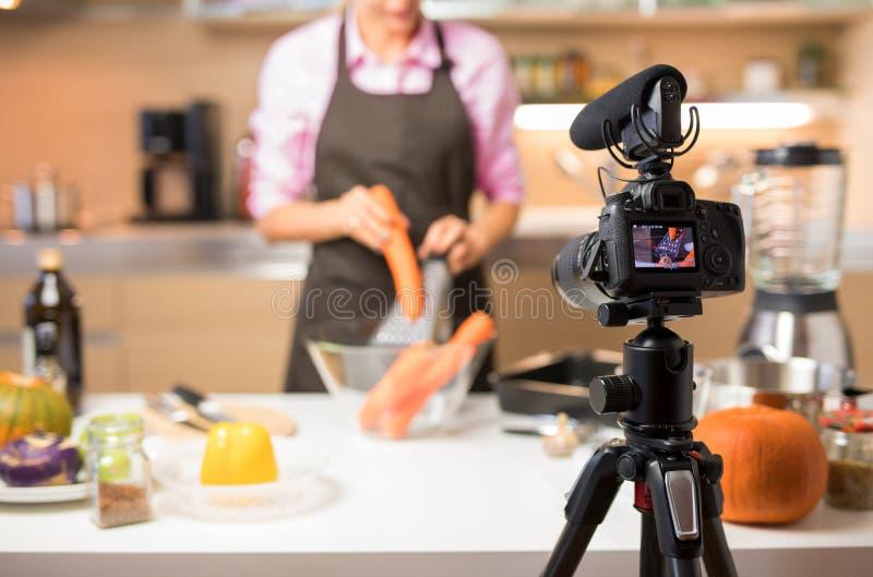 Notierendes Video der Frau von ihr kochend für on-line-Videoblog, Fokus auf Kamera lizenzfreies stockbild