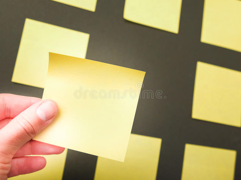 Notification. Hand holding a note against a background with more notes as a great way to expose your slogan or other copy - focus is on the note in hand royalty free stock photo