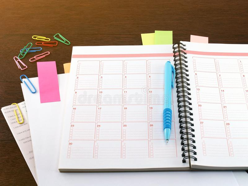 Notitieboekje, blauwe pen, kleverige nota's, leeg document, financiële documenten en kleurrijke paperclip op donkere bruine houte stock foto's
