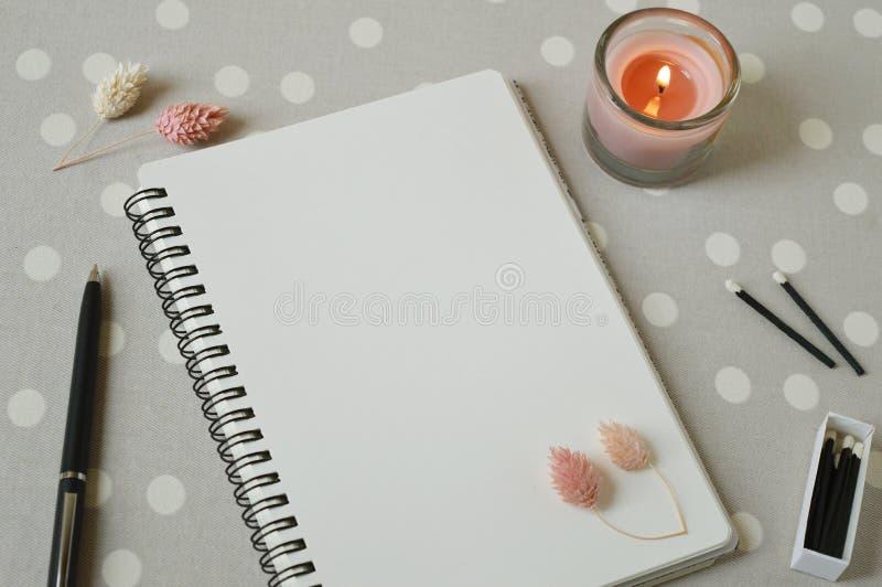 Notitieboekje, een pen, zwarte houten gelijken, koraalkaarsen, droge bloemen op de lijst stock afbeelding