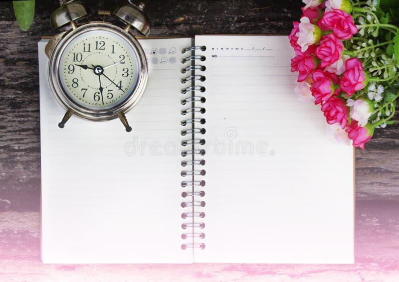 Notitieboekje en bloemen Retro wekker met datum royalty-vrije stock foto