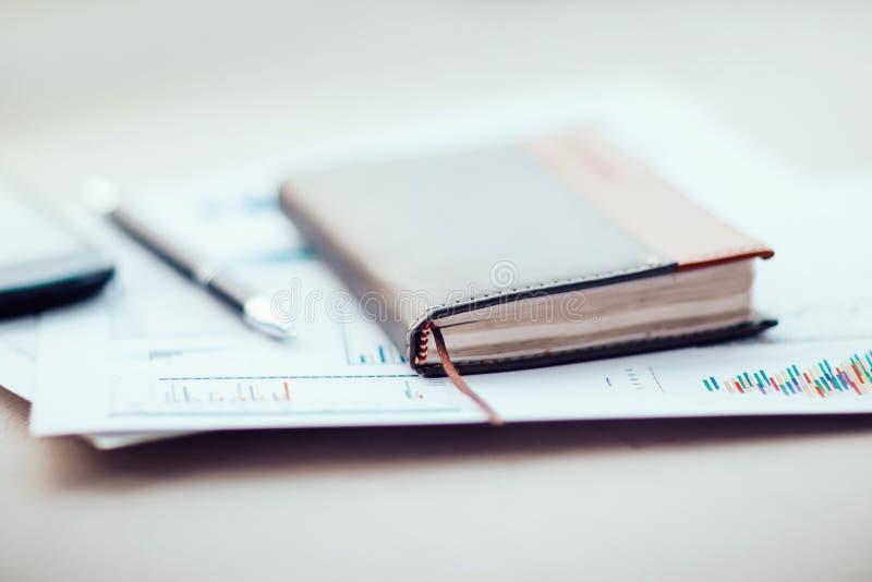 Notitieboekje en financiële grafiek op het Bureau stock foto's
