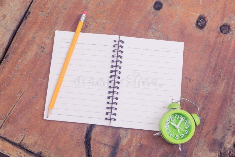 Notitieboekje en groene klok stock foto