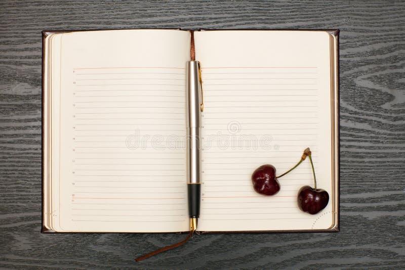 Notitieboekje en kers stock foto