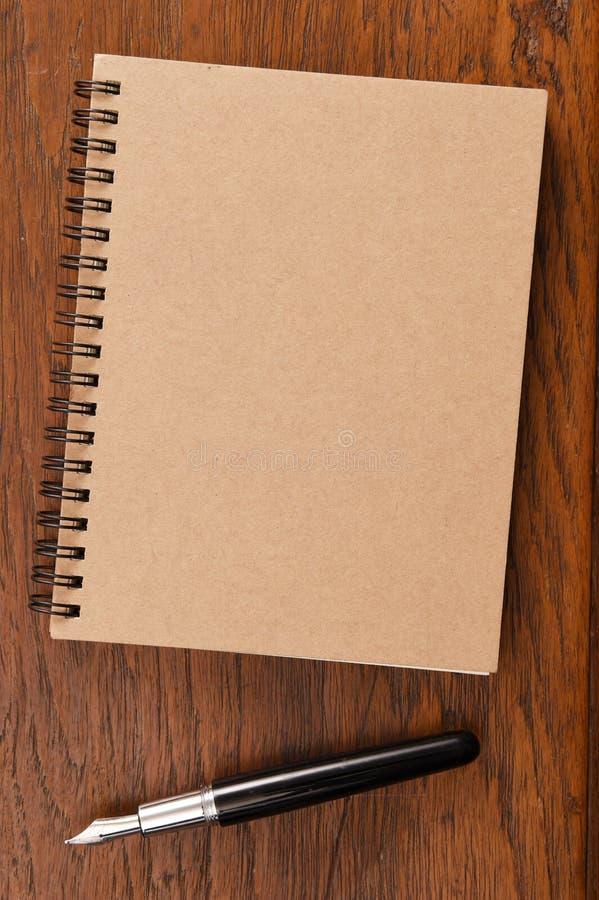 Notitieboekje en pen op houten achtergrond royalty-vrije stock afbeelding