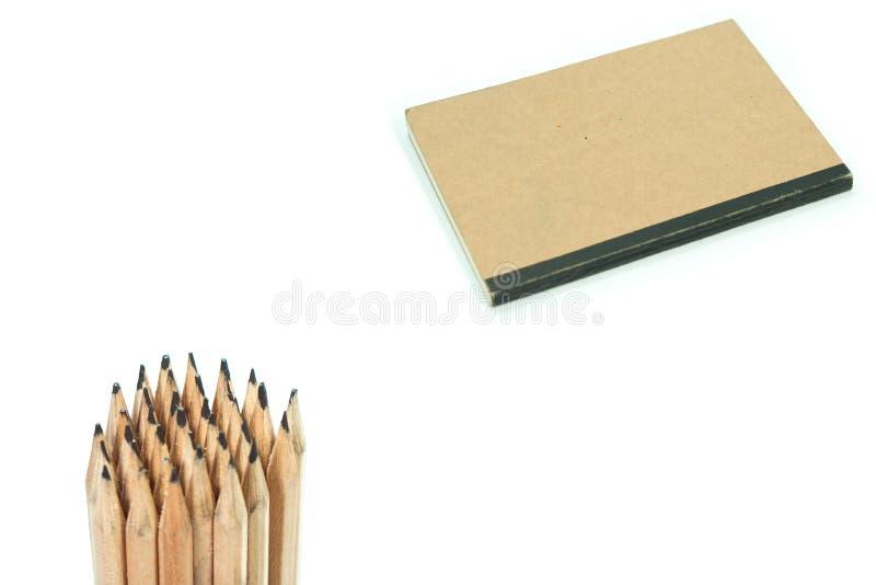 Notitieboekje en potloden op witte achtergrond wordt geïsoleerd die stock fotografie