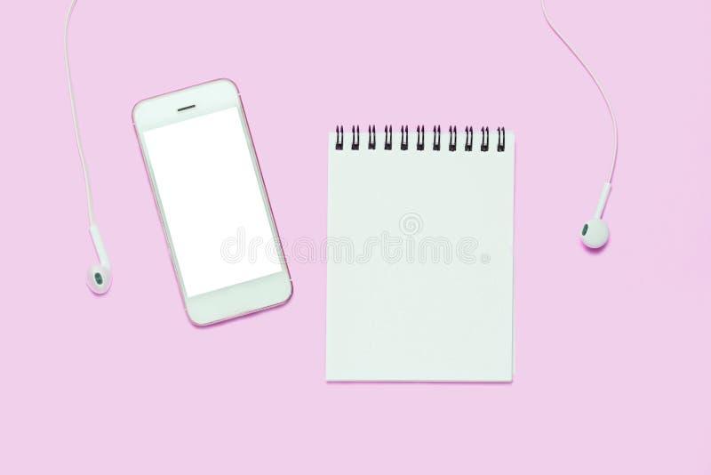 Notitieboekje en smartphone met hoofdtelefoons op roze achtergrond stock afbeelding