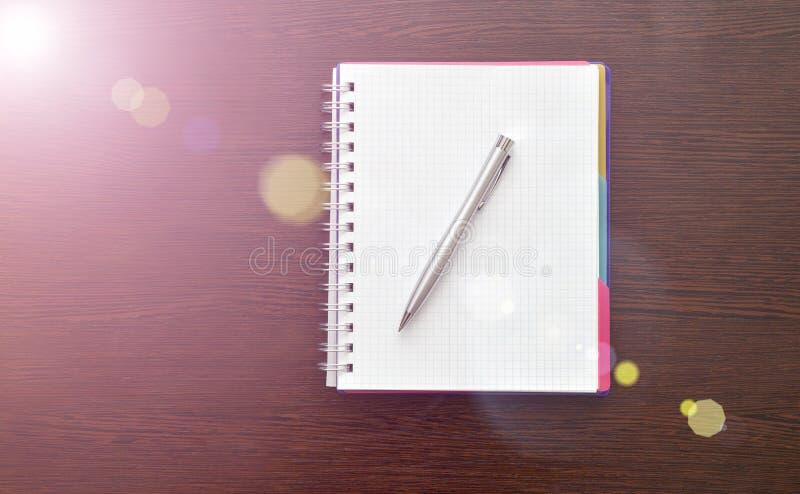 Notitieboekje en staalpen op de lijst met zonlicht royalty-vrije stock afbeelding