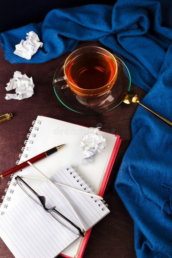 Notitieboekje met blanco pagina, belemmerd document, pen, glazen en kop thee of koffie stock foto's