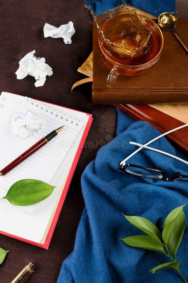 notitieboekje met blanco pagina, belemmerd document, pen, glazen en theekop met het bespatten van thee Schrijvers` s werkplaats royalty-vrije stock afbeelding