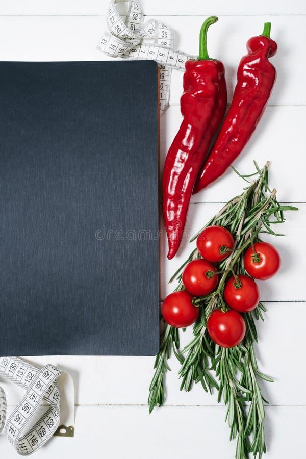 Notitieboekje met een metende band, rozemarijn, peterseliewortel, kersentomaten, Spaanse peperpeper op een uitstekende witte hout royalty-vrije stock afbeelding