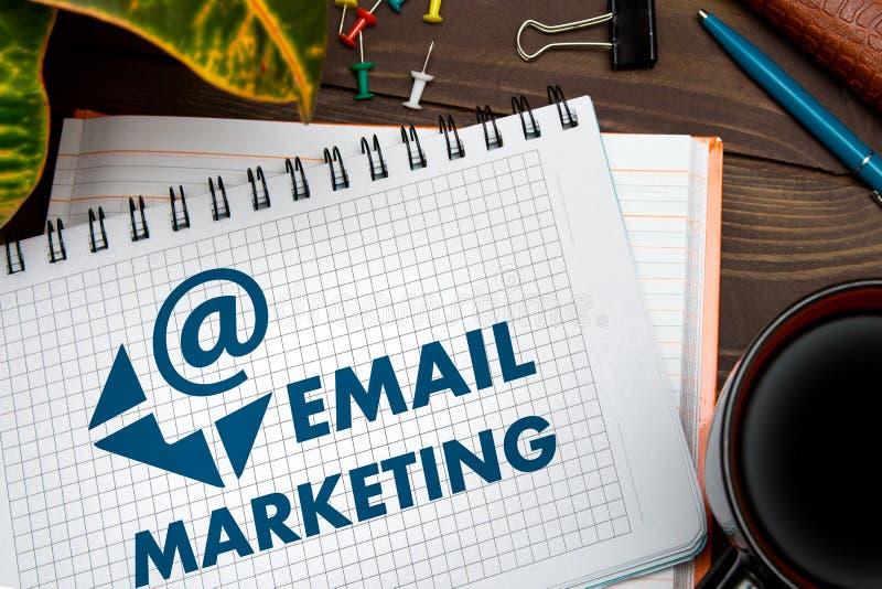 Notitieboekje met een nota's e-mail MARKETING op de bureaulijst met hulpmiddelen Bedrijfs concept stock foto