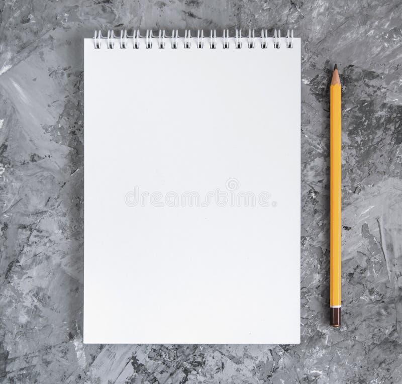 Notitieboekje met een potlood op een concrete achtergrond stock afbeeldingen