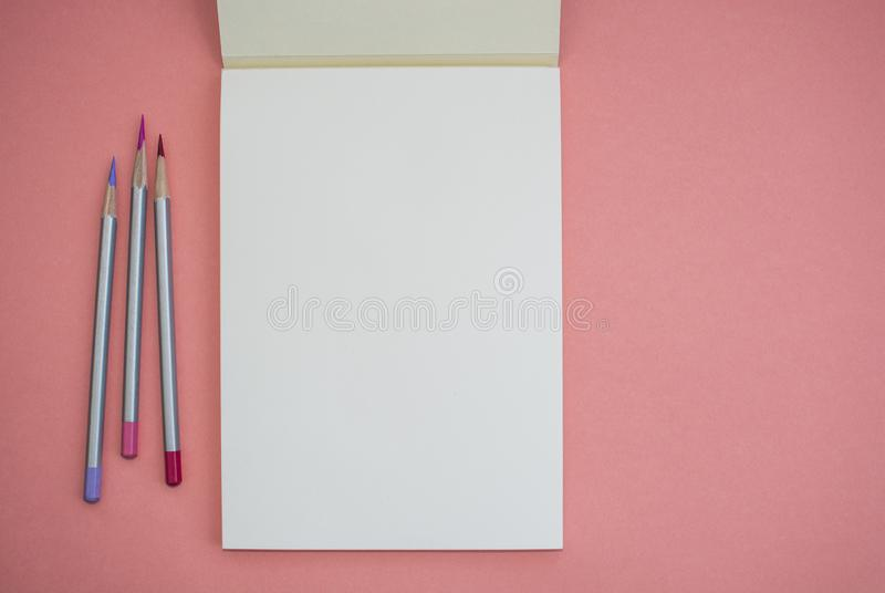 Notitieboekje met een potlood op een roze achtergrond royalty-vrije stock foto