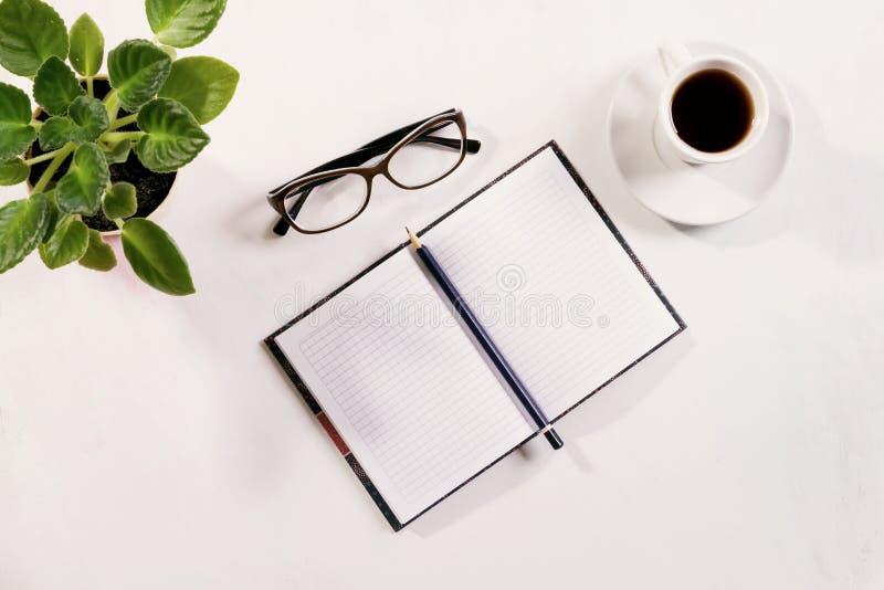 Notitieboekje met glazen en koffie op lijst stock afbeeldingen
