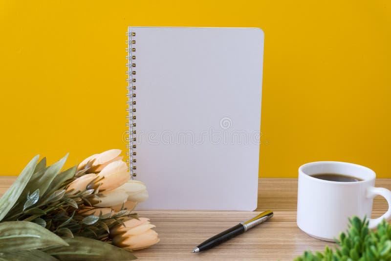 Notitieboekje met koffiekop en bloem op houten bureau met gele achtergrond royalty-vrije stock afbeeldingen