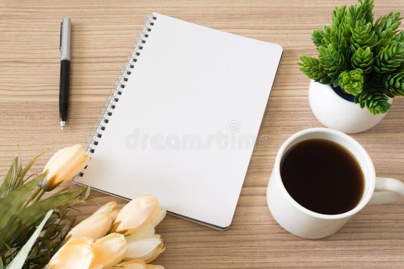 Notitieboekje met koffiekop, ingemaakte installatie en bloem op houten bureau royalty-vrije stock foto's