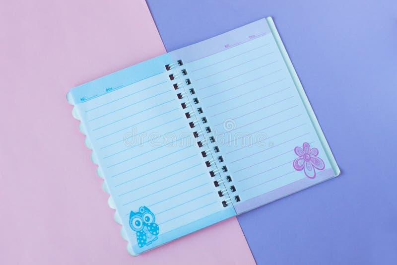 Notitieboekje met lijnen Schoolkantoorbehoeften op een roze en purpere duotoneachtergrond royalty-vrije stock afbeeldingen