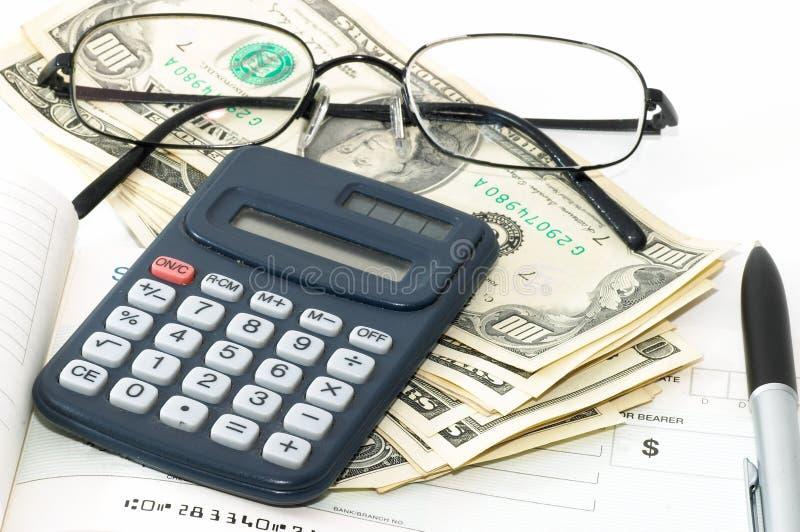 Notitieboekje met pen, calculator, chequeboek, contant geld en glazen stock afbeelding