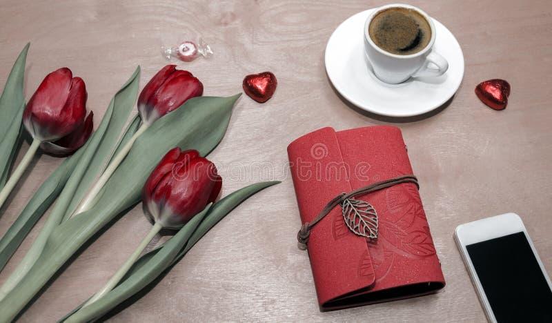 Notitieboekje met pen en telefoon, kop van koffie en tulpen royalty-vrije stock foto's