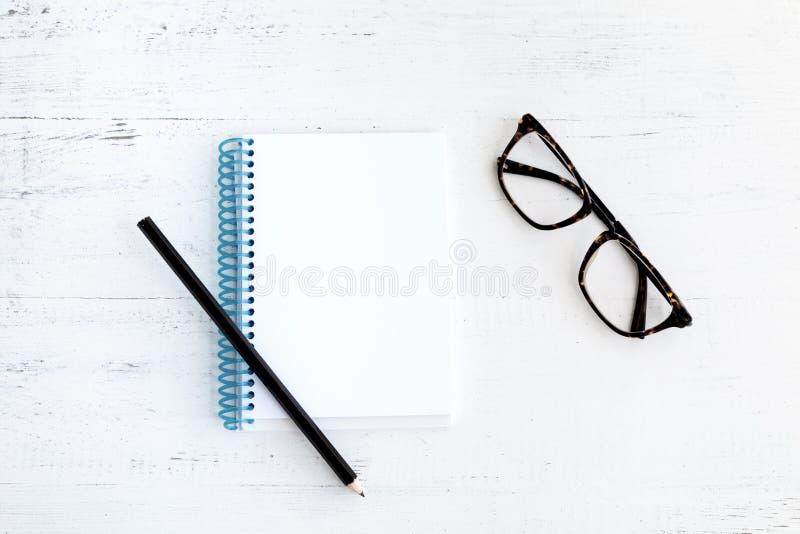 Notitieboekje met potlood op hout en glazen stock fotografie