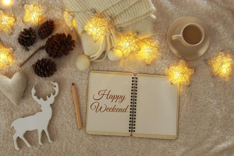 Notitieboekje met tekst: GELUKKIG WEEKEND en kop van cappuccino over comfortabel en warm bonttapijt Hoogste mening stock fotografie