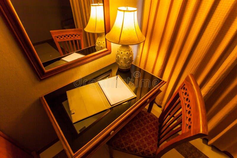 Notitieboekje op de lijst met lamp en stoel in retro stijl stock foto