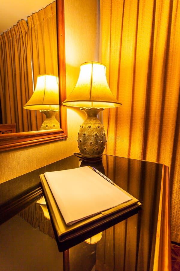 Notitieboekje op de lijst met lamp in retro stijl stock afbeeldingen