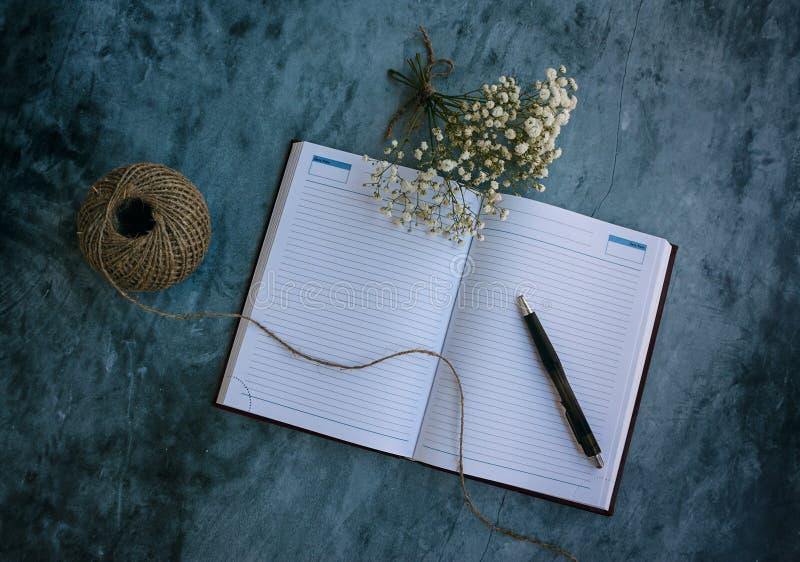 Notitieboekje, pen en bloemen stock afbeelding