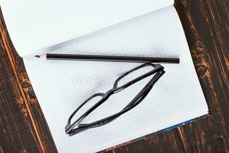 Notitieboekje, pen en glazen op een houten lijst De ruimte van het exemplaar stock afbeeldingen