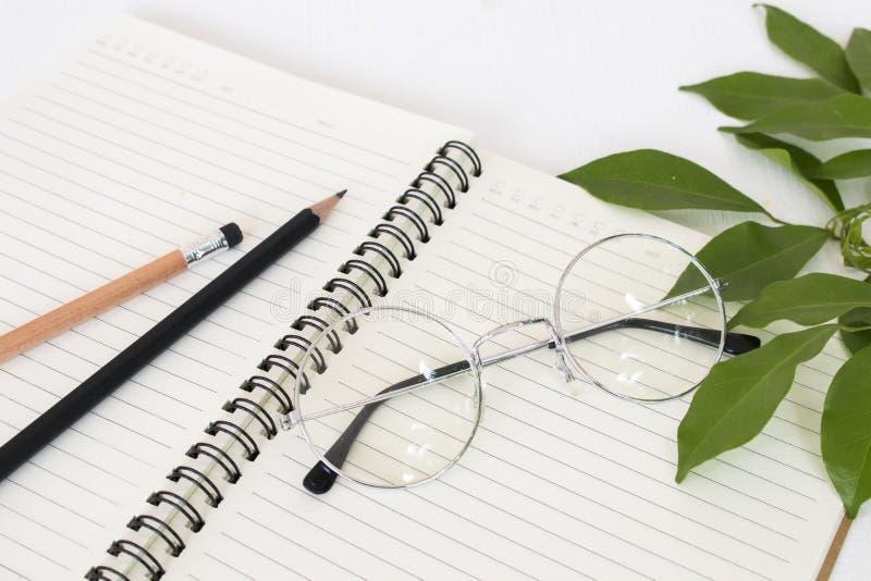 Notitieboekje voor mededeling met potlood, bril royalty-vrije stock foto