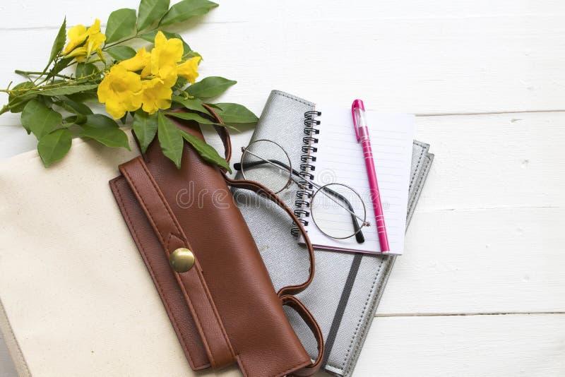 Notitieboekjeontwerper voor het bedrijfswerk met handtas, bril en bloem stock afbeelding
