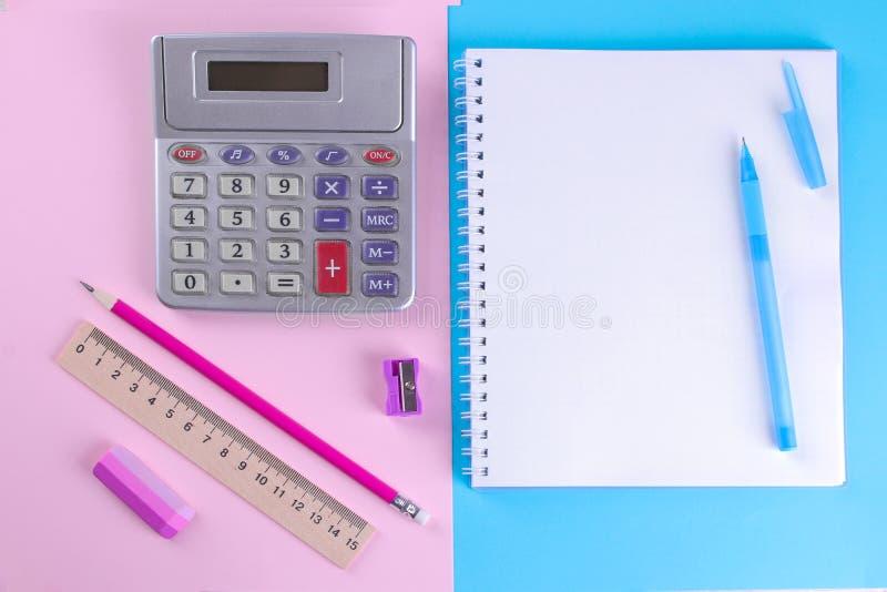 Notitieboekjes en een calculator met verschillende kantoorbehoeften op een heldere oranje en groene achtergrond De levering van d stock foto's