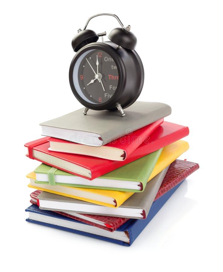 Notitieboekjes en wekker bij witte achtergrond stock afbeelding