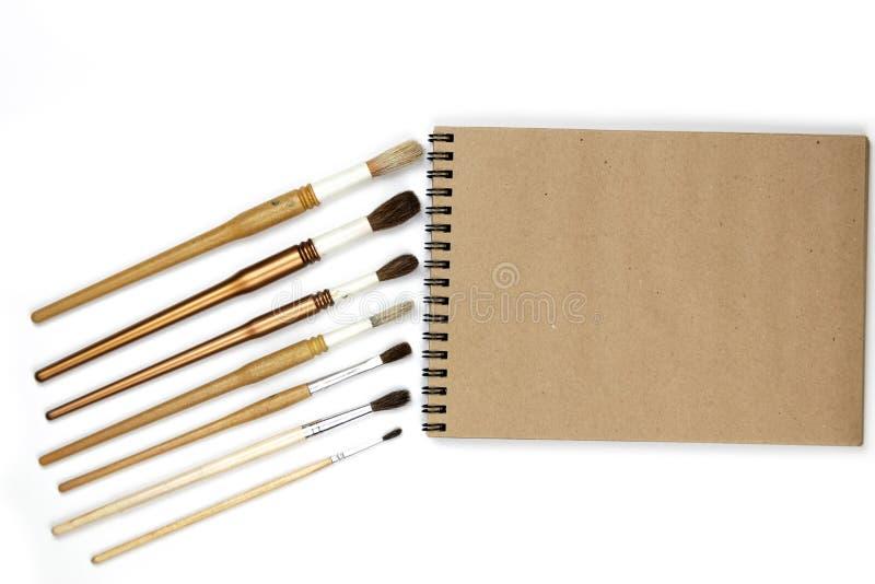 Notitieboekjespot omhoog voor kunstwerk met waterverfverven die op witte achtergrond worden ge?soleerd stock fotografie