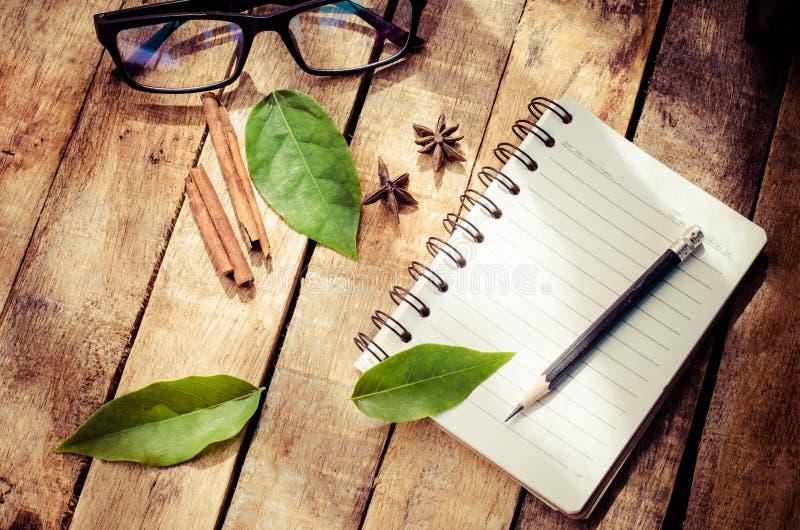 Notizbücher, Bleistifte, Ausrüstung auf dem Bretterboden mit der Morgensonne, die schwach scheint stockfoto