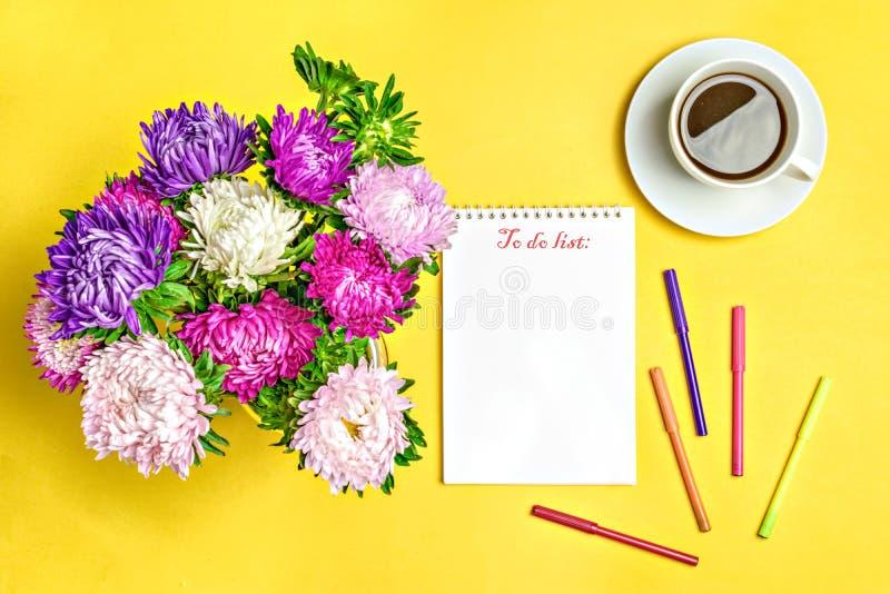 Notizblock, Asterblumen, färbte Filzstifte, Schale mit Kaffee auf gelbem Hintergrund Konzeptherbst, Sommer, Frühling stockfoto