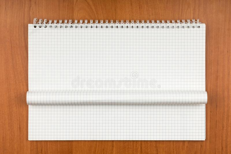 Notizblock auf einer Spirale mit einem gekräuselten Blatt, das auf einer Tabelle liegt stockfotografie