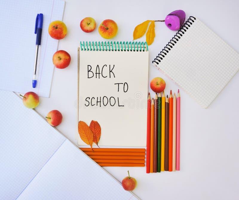 Notizblock mit Bleistiften, Herbstlaub und Äpfeln auf weißem Hintergrund Zur?ck zu Schule-Konzept Wie eine Suppe befestigt lizenzfreie stockfotos
