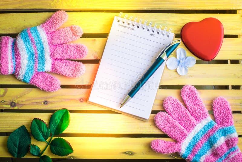 Notizblock mit Handschuh auf hölzernem Bretthintergrund unter Verwendung der Tapete für Bildung, Geschäftsfoto Nehmen Sie zur Ken lizenzfreies stockfoto